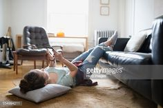Stockfoto : Woman laying with feet up texting cell phone