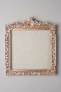 this would be so easy to make with a cheap frame, gold spray paint and some fabric - you could use it to pin photos and such on!!