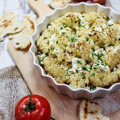 Kalafior zapiekany w pikantnym pomidorowym sosie. Kalafior pieczony po grecku, na pomidorach, cebuli, czosnku i kaparach, posypany fetą.Lekki obiad z kalafiora.