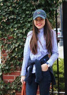 New England Classic Style | Blue Oxford shirt | Jeans | Navy jumper tied at the waist | Navy baseball cap