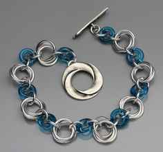 SPIRAL WEAVE FAMILY Spiraling flowers are segmented by pressed glass rings in this great beginners pattern. Students will learn all the basic chainmaille weaving techniques and complete a full bracelet rather quickly. Students can choose from aluminum or copper in combination with a variety of glass ring colors to choose from.
