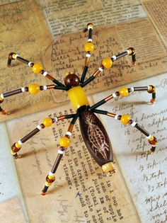 http://atomicrose.blogspot.com  Lots of beaded spiders for inspiration.  I love making them with middle school kids who need fine motor practice and that are often boys. They work to make them realistic.  Materials: wood beads, plastic yellow bead; brown E beads; round yellow beads; black, brown, and red bugle beads; red, bone, and mustard yellow seed beads, gold wire