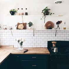 Black cabinets, wood countertops, and white subway tile. Kitchen Tiles, New Kitchen, Kitchen Dining, Kitchen Decor, Kitchen Black, Kitchen Plants, Gold Kitchen, Home Interior, Kitchen Interior