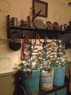 Primitive Early American Christmas Trees ~ Great handmade easy DIY country look   by EarlyPrimfolksbyjudy.  Beautiful prim grouping with black shelf, blue wood buckets, pewter and colonial painted wall stencils.