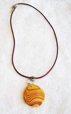 Red and yellow pendant with red leather necklace.