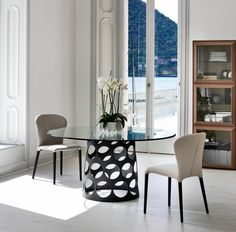 An elegant circular dining table with a clear glass top and a unique leg from Porada.