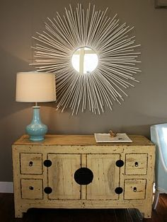 Buy a cheap round mirror and hot glue dowel rods to back of mirror (spray paint rods any color you want)... really like this!