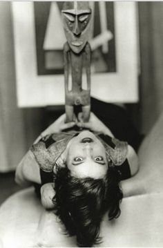 """Around 1927, Man Ray staged this appropriately Surrealistic scene by posing """"Simone Kahn,"""" wife of Surrealist leader Andre Breton, lying on her back and gazing at the viewer, while holding on her stomach a sculpted Vanuatu male figure from eastern Malekula. Photography, Surrealism and African art were a popular combination for a time.  from the exhibition'Man Ray, African Art And The Modernist Lens' atThe Phillips Collection"""