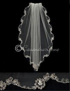 A silver embroidered flower and vine design accents the edge of this scalloped bridal veil. Each flower is enhanced with round, teardrop and marquise rhinestones, silver lined seed beads are scattered