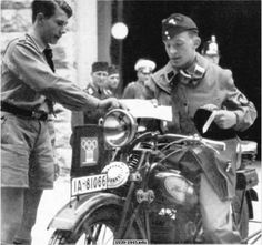 One of the many diligent Olympic workers. A courier of the National Socialist Motor Corps receives photographic material from a Hitler Youth. Olympic Games, Berlin, 1936