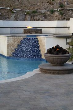 A spacious swimming pool has a built-in raised hot tub and fire pit. Blue mosaic tile covers the stairs to the hot tub area, giving the illusion of a continuous stream of water. A second fire pit is positioned on the swimming pool patio. Outdoor Living Areas, Outdoor Spaces, Blue Mosaic Tile, Pool Designs, Backyard Designs, Backyard Ideas, Art Deco Living Room, Fire Pots, Outdoor Seating
