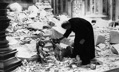 One of the clergy of St. Paul's cathedral in London looks at two cherubs standing among the debris and holding their heads as though for protection, Oct. 10, 1940. (AP Photo)