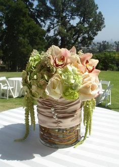 """""""Roses, hydrangea, cymbidium orchids and other blooms are beutifully arranged in this custom centerpiece. The vase is wraped in champagne silk with freshwater pearls cascading down to add a touch of elegance."""" Church Wedding Flowers, Cymbidium Orchids, Flower Ideas, Hydrangea, Champagne, Centerpieces, Roses, Bloom, Touch"""
