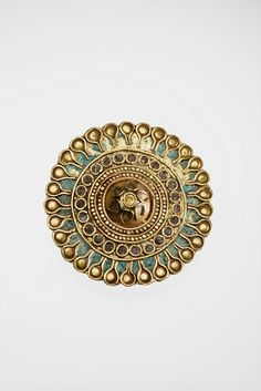 Gold and enamel ear stud. Conventional design in cloisonné with paste inlay. A granulated double band surrounds the raised rosette in the center . The rim decoration shows a floral wreath over a blue inlaid ground.