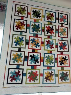 Twisted square dance quilt quilted by Patches and Piecework Quilting, hanging in Piece to Peace Treasures.