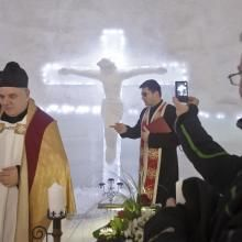 A man shoots video on a mobile phone of Romanian priests inside at church built entirely from ice blocks cut from a frozen lake before a blessing religious service at the Balea Lac resort in the Fagaras mountains, Romania, Thursday, Jan. 29, 2015. The blessing was performed jointly by priests from all Christian denominations in Romania and the church, built at an altitude of over 2,000 meters, will host all types of religious events like weddings and baptizing ceremonies as long as the cold…