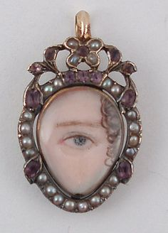 Eye Miniature painted on ivory - Georgian C. 1790 -   Blue eye miniature hand painted on ivory under ovoid rock crystal with foiled garnets and pearls frame, hinged at the top, surmounted by a pearl-set flower motif and bail. (see pg 35 Romero 3rd)