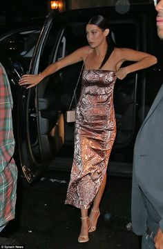 Metallic magic:Featuring a daring split, the form-fitting garment highlighted the brunette beauty's slim physique to perfection as she enjoyed her night out on the town alongside a rather stylish crowd