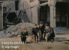 2-G55-F1-1917-44 Autochrome showing children playing in front of a ruined house in Reims, Place Drouet d'Erlon, early 1917 akg-images