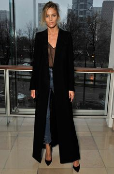 Anja Rubik usa blusa de transparência preta, maxi casaco preto, jeans de cintura alta e arremata com scarpin preto