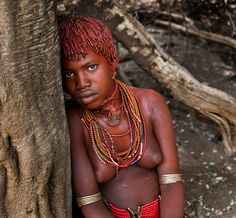 This is Galtier, a young woman from the Hamer tribe. Galtier has the traditional red hair and skin made from red clay, butter and animal fat.