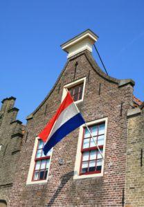 Dutch flag flying on typical Dutch house