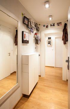 Vstupní chodbu opticky zvětšuje bílá barva i velké zrcadlo, vtipným řešením pro zavěšení kabátů i upomínkových předmětů jsou lanka u stropu - ProŽeny.cz