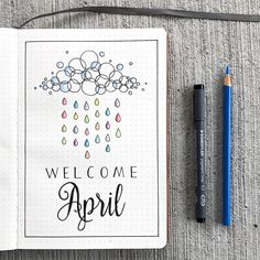 Bullet journal monthly cover page, April cover page, rain cloud with colourful raindrops drawing. |