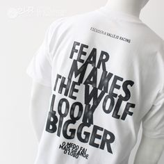 """Prenda de alta calidad, unisex,  tejido: 100% algodón, hilo Belcoro®, rojo Jaspeado 97% algodón , 3% poliéster, peso 185gm/m² Colores – 195gm/m², cuello redondo ribeteado con tapeta para mayor confort.    Camiseta blanca con serigrafía gris a gran tamaño en costado y espalda. Costado derecho con icono a gran tamaño de lobo oficial y espalda diseño erosionado con lema """"Fear Makes the Wolf Look Bigger""""."""