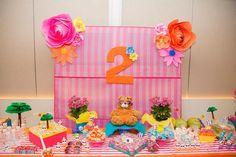 Mesa linda e cheia de toques rosa e laranja para a festa de dois anos de uma menina. O tema escolhido foi praia e o painel feito com esteiras de praia e flores gigantes de papel.: