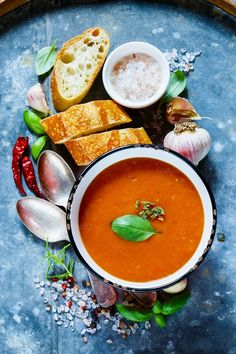 #Tomato soup Gazpacho  Tasty tomato soup Gazpacho in rustic metal bowl with fresh baguette chili garlic and basill on old rusty iron background top view.
