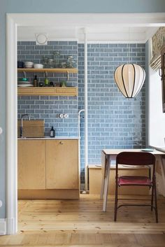 Swedish kitchen, a pretty surprising colour combination of light wood cabinets, open shelves and blue tiles.