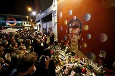 Fans stand by floral tributes at a mural of David Bowie in Brixton