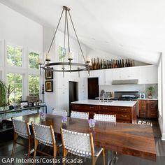 Der rustikale Kronleuchter mit Kerzen dominiert diesen offenen Küchen- und Essbereich. Der ausladende Tisch aus Massivholz und dazu passende Küchenschränke…