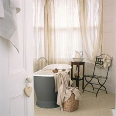 Bathroom with freestanding bath, sheer curtains and sisal carpet | housetohome.co.uk