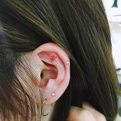 Tiny red flower tattoo on the left ear.
