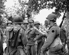 A German officer smiles as he is interrogated by American soldiers who landed on the beaches of Normandy, France on June 12, 1944.