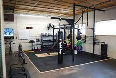 Dedicated garage gym complete with flooring, rack, GHD, and bag #train #box