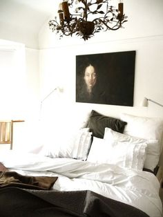 White bed offset by dark asymmetric portrait overhead. Euro Shams, no headboard.