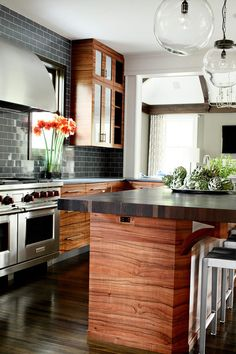 love everything about this kitchen - gorgeous wood on cabinets and island, gray subway tile, glass pendants, via ML Interior Design