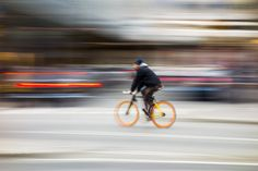 Cyclist in traffic on the city roadway - Cyclist in blurred motion against a background of an urban landscape Mood Images, Urban Landscape, Bicycle, City, Photography, Photograph, Bicycle Kick, Fotografie, Bike