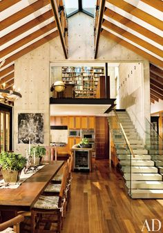 At a Southern California ranch by Geoff Sumich Design, the ironwood table and chairs decorate the great room's dining area. Dogger, by Elliott Puckette, hangs on the concrete column. The stairs lead to the library, which is suspended above the kitchen. Architectural Digest, Casa Loft, Interior Architecture, Interior Design, Dining Area, Dining Table, Kitchen Dining, Kitchen Decor, Great Rooms