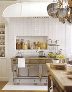 The yellow crocks above the stove really bring out the beauty of the brushed brass trim on the range. I am not a fan at all of subway tile, but with the stove the star of the kitchen, I can accept it, kinda.   source-House Beautiful