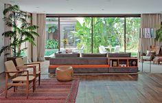 O sofá cinza tem um banco e módulos nas costas. Estes elementos dão um toque de cor vibrante, laranja, à decoração neutra. O modelo é uma boa opção para quem não vai encostar os assentos na parede. Projeto do Estúdio Cada Um
