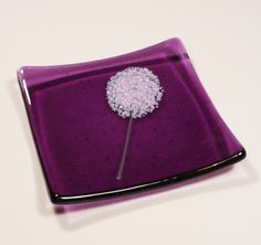 A lavender flower with a green stem is fused onto purple transparent glass to create a beautiful fused glass dish. The edges of the square shape Slumped Glass, Fused Glass Plates, Fused Glass Jewelry, Fused Glass Art, Glass Dishes, Mosaic Glass, Stained Glass Birds, Glass Fusion Ideas, Glass Fusing Projects