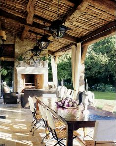 .gorgeous outdoor living and dining area.  Love the fireplace, lighting, drapes, etc.