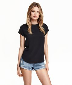 Check this out! Short-sleeved, gently flared blouse in woven crêpe fabric with a button at back of neck. Rounded hem, slightly longer at back. - Visit hm.com to see more.