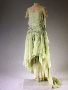 Callot Soeurs evening dress, 1929 From the Hillwood Museum This dress and cape ensemble were worn by Mrs. Post for her presentation at the Court of St. James's. The tubular dress is sleeveless with dropped waistline and slightly flared at bottom. The flesh colored organza bodice and skirt are cut in one piece. A green organza skirt is attached at the dropped waist. The garment is heavily beaded on the side seams and waist, both back and front, with rhinestones and clear bugle beads Back 2