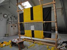 A photo of a large square yellow and black loom weaving