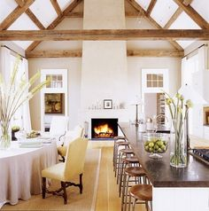 Cozy living space with open floor plan, wooden beans, and a fireplace